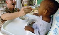 Chaplain (Maj.) Steven O'Brien feeds an orphaned toddler mashed potatoes at the Franciscan Missionaries of Notre Dame Baby Orphanage in Djibouti City, Djibouti. Chaplain O'Brien deployed to Camp Lemonier, Djibouti, from the 4th Air Force at March Air Reserve Base, Calif. The Camp Lemonier chapel staff arranges visits to this orphanage three times a week. (U.S. Air Force photo/by Staff Sgt. Francesca Popp)